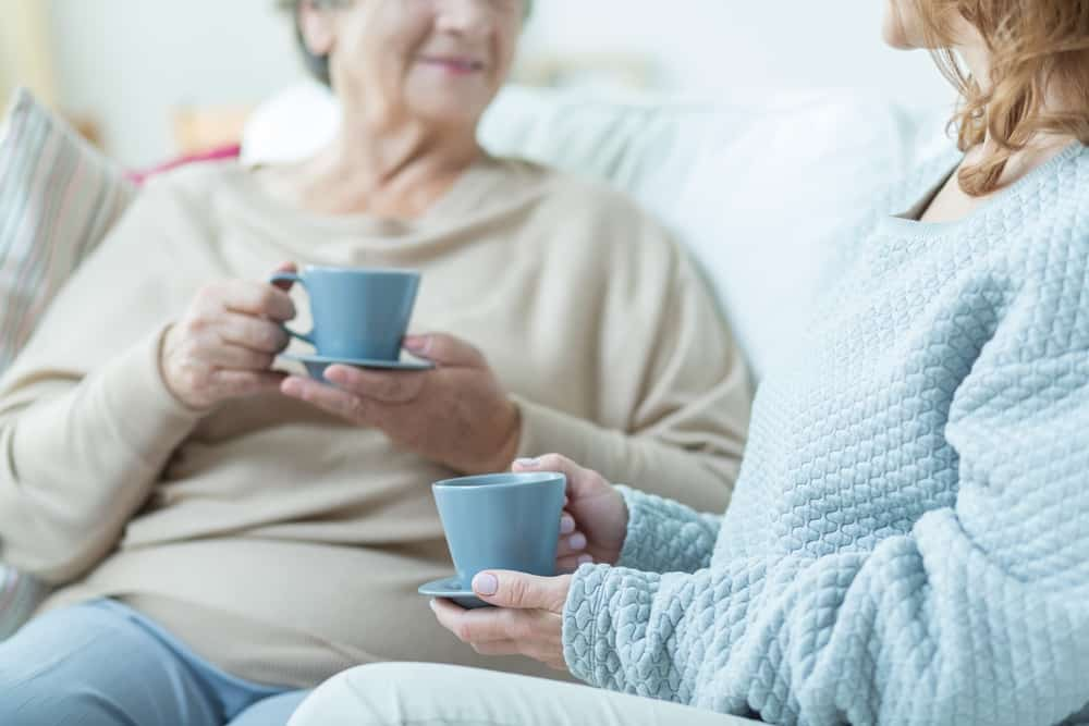 old people drinking coffee on couch blue mugs