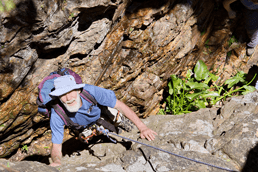 rock climbing man with blue shirt and hat mountain