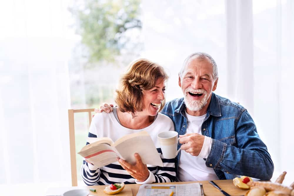 old couple reading book and drinking coffee