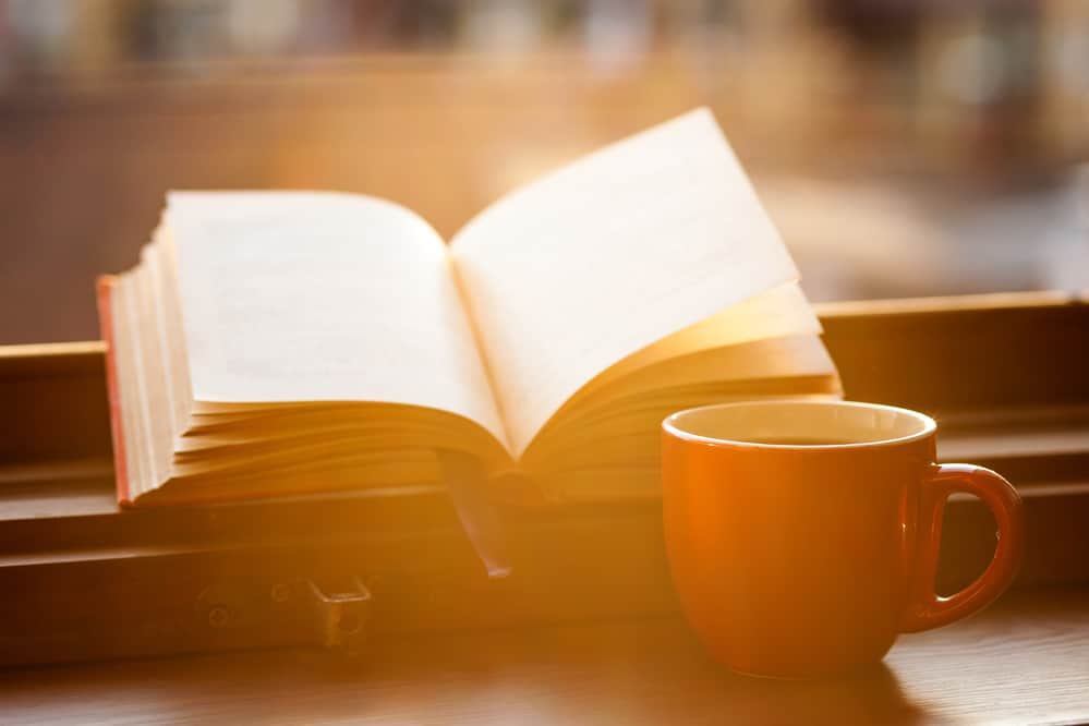 coffee in red mug book in sunlight