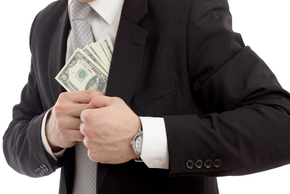 man in suit putting money into pocket