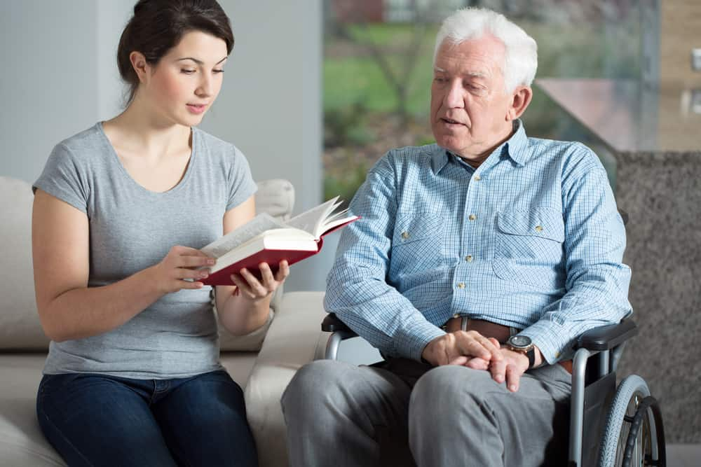 caregiver woman with senior man reading aging iq