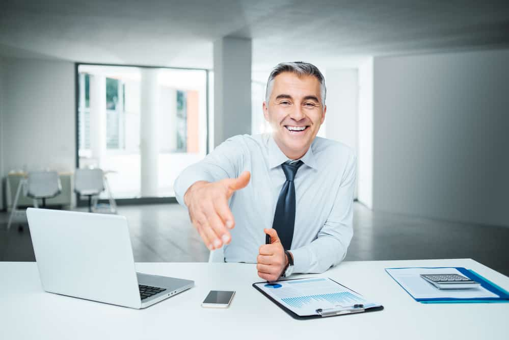 agent smiling shaking hands laptop and office