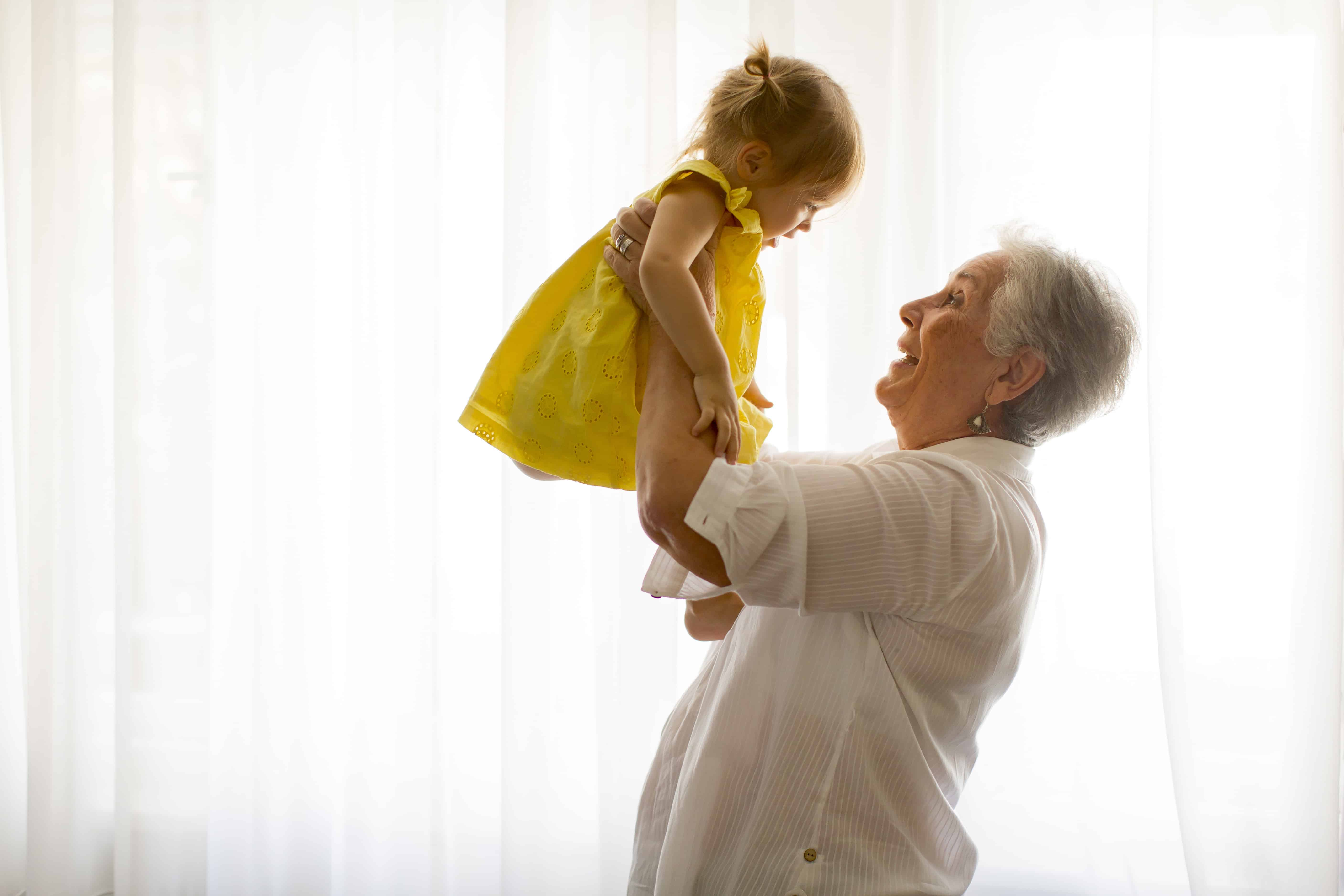 old woman holding baby in yellow dress