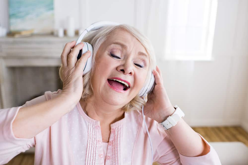 old woman pink shirt singing while wearing headphones