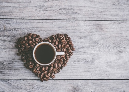 Coffee beans in heart shape with mug