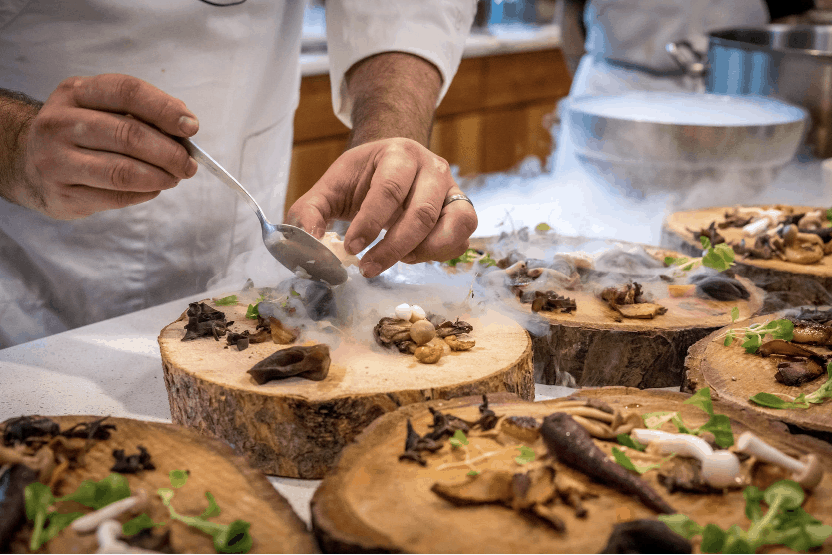Chef plating food on wood