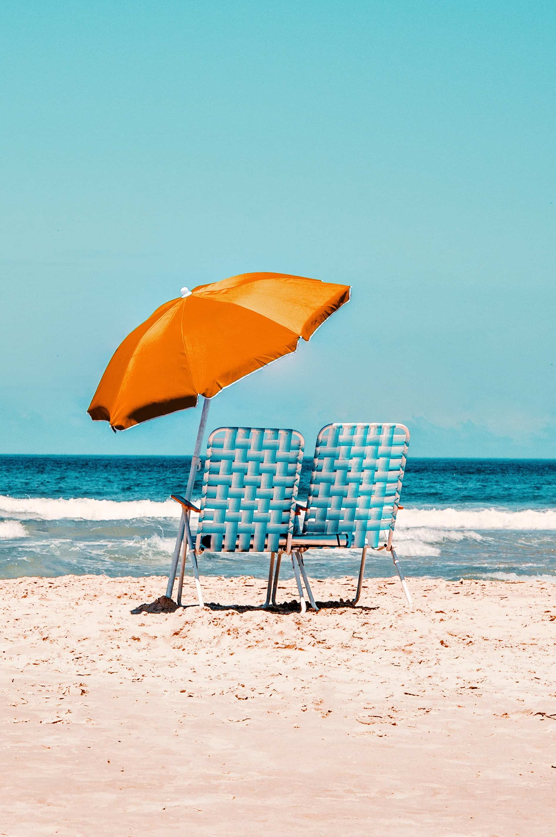 Orange parasol on beach with blue beach chairs