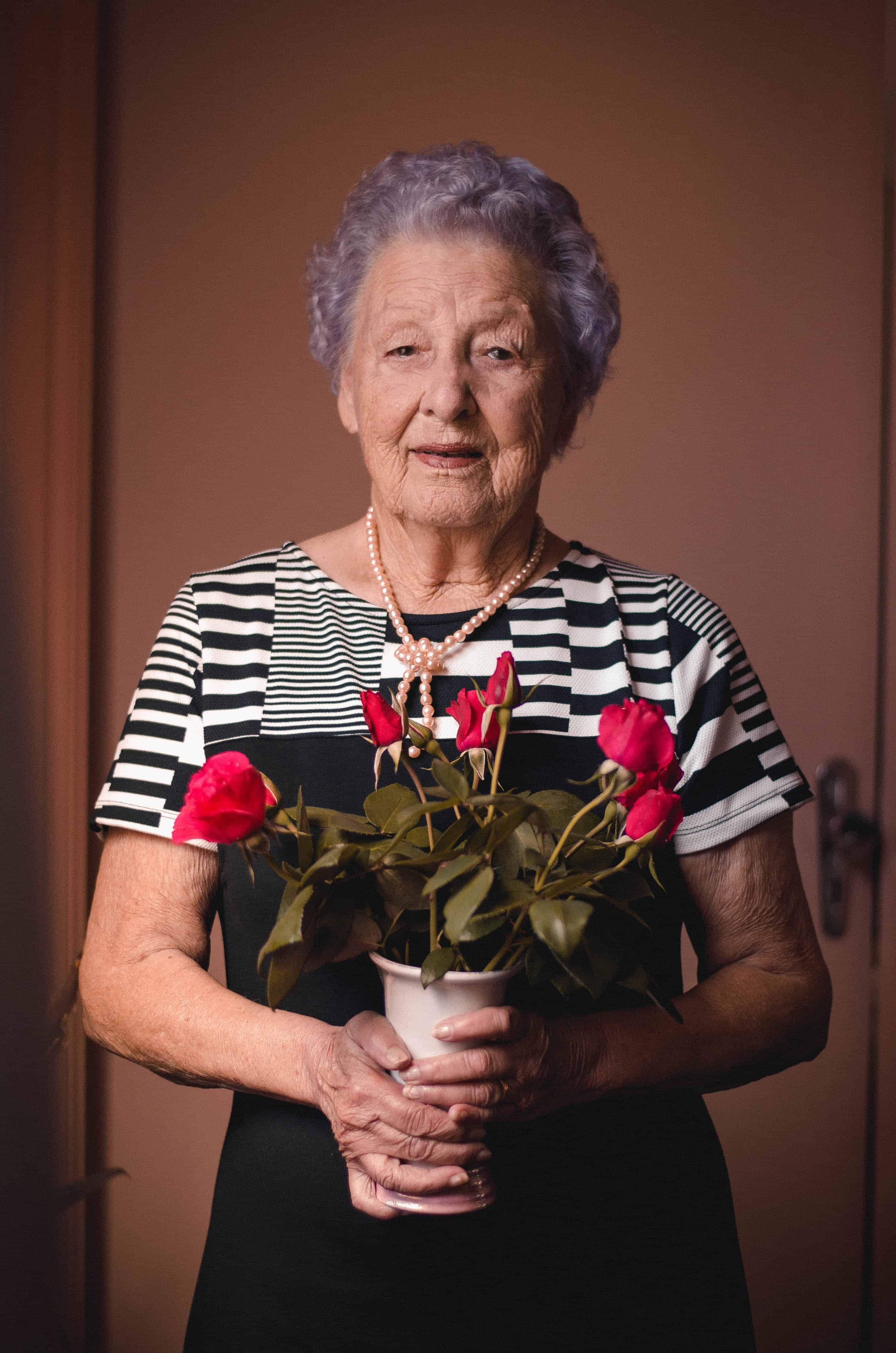 Old Age Grandmother old woman holding red flowers