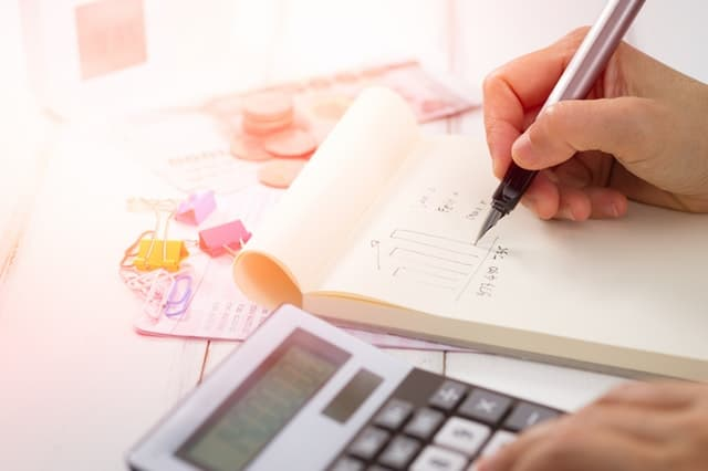 Planning your estate hand writing on notepad while using calculator