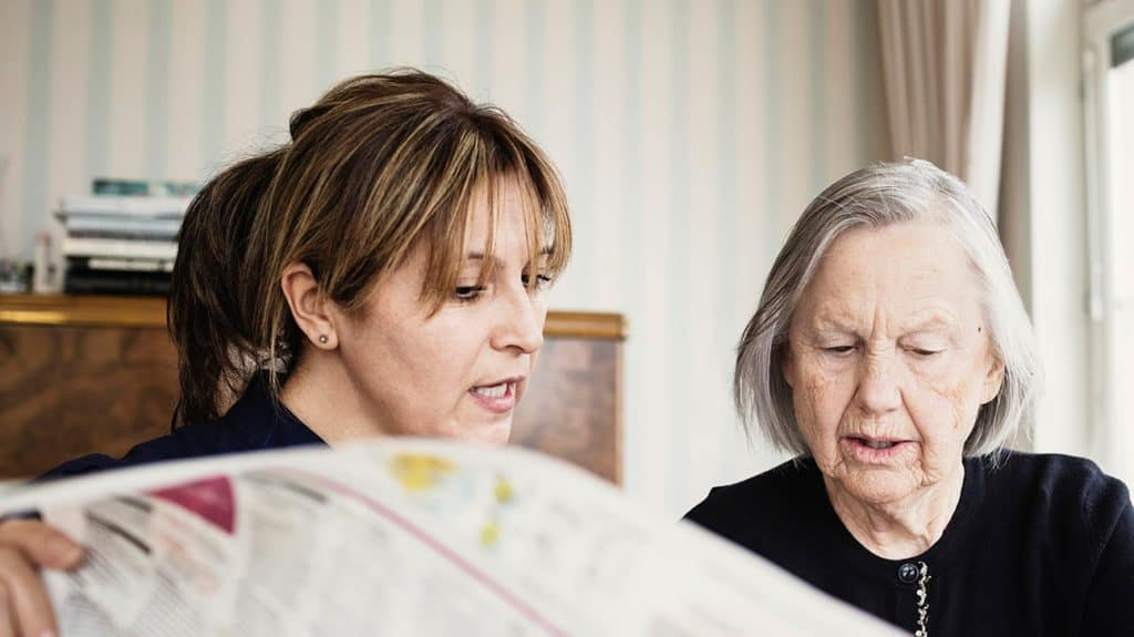 woman reading newspaper with elderly woman
