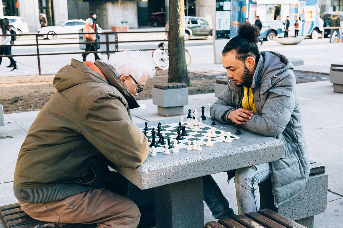 young and old man playing chess in park