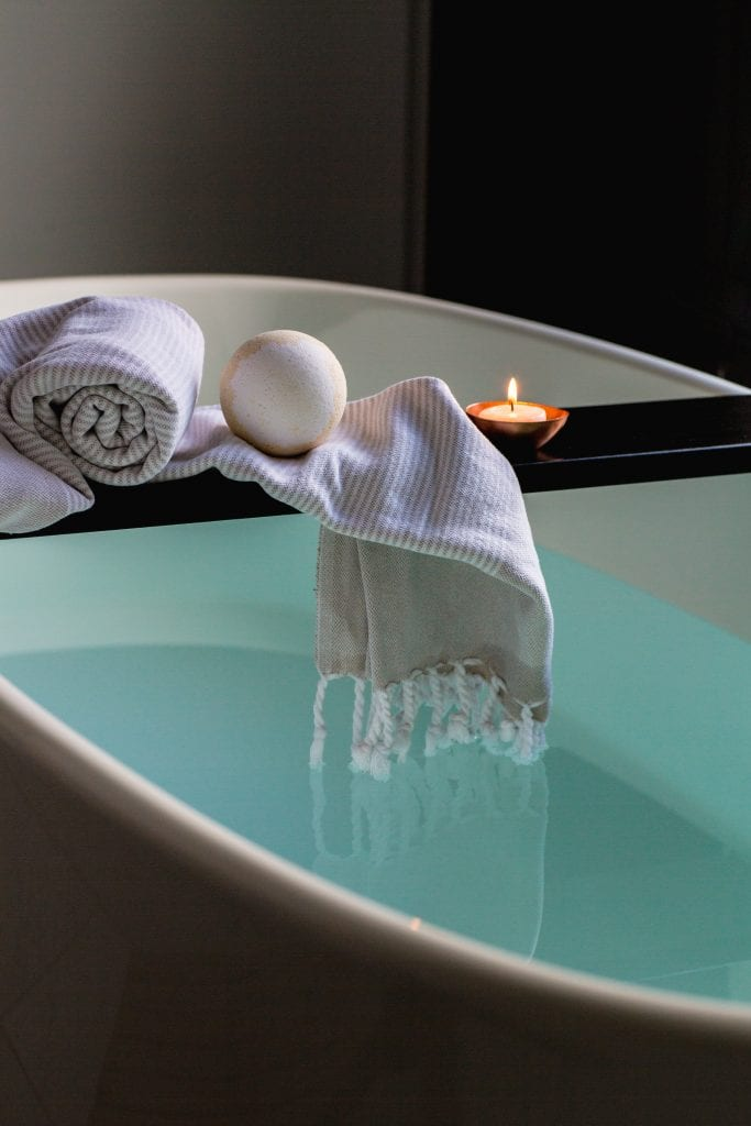 Bath tub indoors with towel and candle relaxation