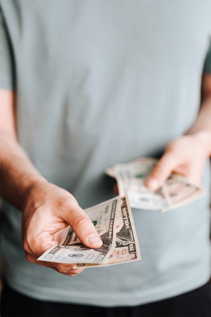 (credit: Karolina Grabowska) man paying with american dollars