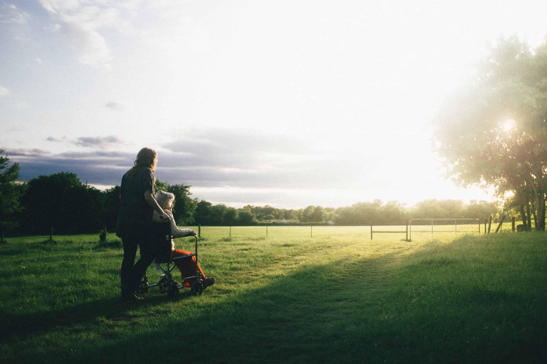 caregiver pushing woman in wheelchair through field