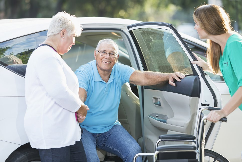 (credit: Getty Images) caregiver assisting man out of car and into wheelchair