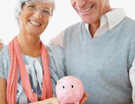 seniors holding piggy bank smiling