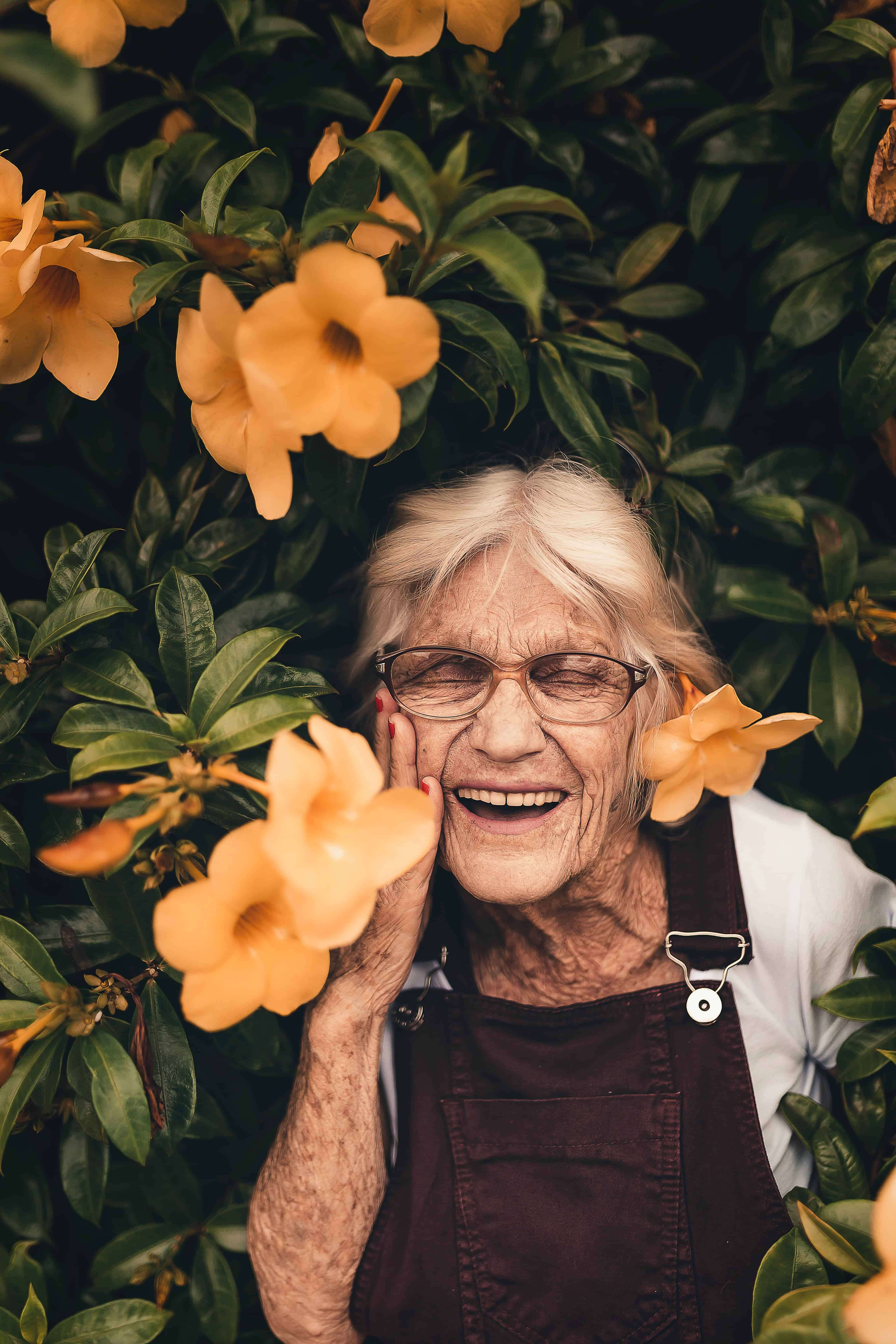 Smiling elderly woman with yellow flowers happiness