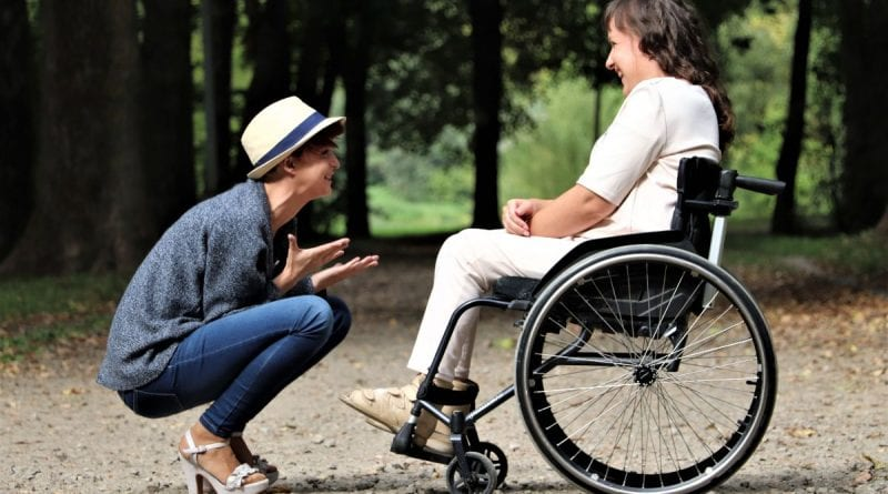 woman talking to lady in wheelchair