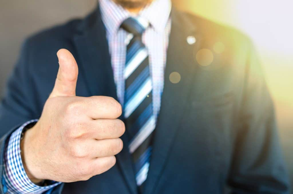man giving thumbs up in blue suit