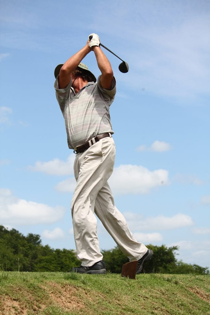 man golfing in gray pants